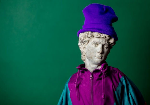 Antique statue dressed in trendy clothes of the nineties on green wall