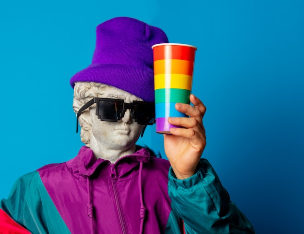 Antique statue dressed in trendy clothes of the nineties holds cup of drink