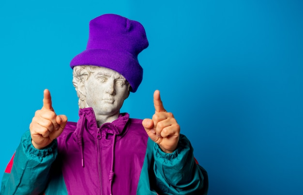 Antique statue dressed in trendy clothes of the nineties point at you