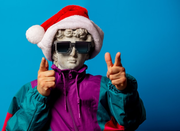 Antique statue dressed in trendy clothes of the nineties and santa claus hat