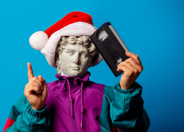 Antique statue dressed in trendy clothes of the nineties with vhs video tape