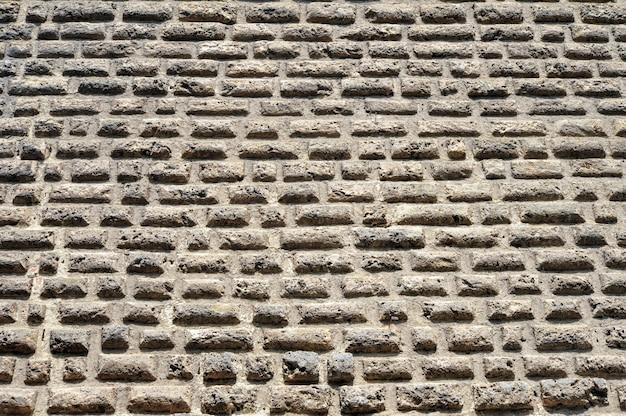 Античная каменная стена из плоского кирпича фон