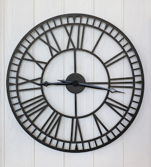 Antique style clock on white wood plank wall background