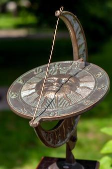 가장자리에 숫자가 있고 중앙에 태양이 있는 아름다운 다이얼이 있는 앤틱 해시계. 팽팽한 와이어 포인터가 있는 산화된 청동 디스크. 선택적 얕은 초점.