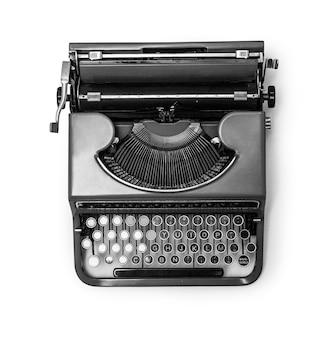 Старинная пишущая машинка на ярко-белом фоне.