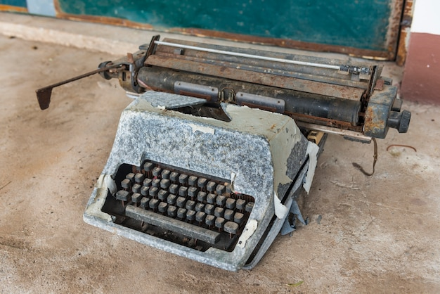 Antique typewriter. vintage typewriter machine closeup photo on cement background.