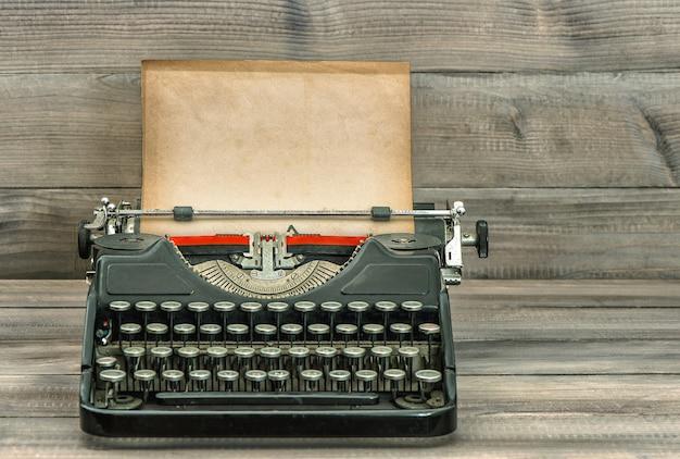 Античная пишущая машинка с шероховатой бумагой на деревянном фоне. тонированная картина в стиле ретро. выборочный фокус