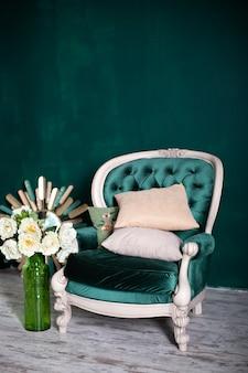 꽃병와 에메랄드 벽 근처 꽃의 꽃다발 골동품 벨벳 녹색 안락의 자. 녹색 배경에 안락의 자 격리 됨입니다. 거실에 빈티지 의자입니다. 가구 집. 클래식 인테리어 그린 소파