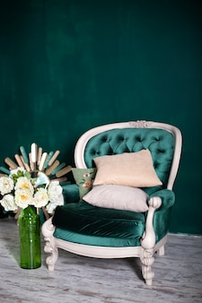 Antique velvet green armchair with a vase and bouquet of flowers near emerald wall. armchair isolated on green background. vintage chair on living room. furniture home.  classic interior green sofa