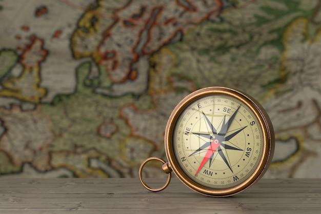 Античный винтажный латунный компас на деревянном столе перед крайним крупным планом античной карты. 3d рендеринг