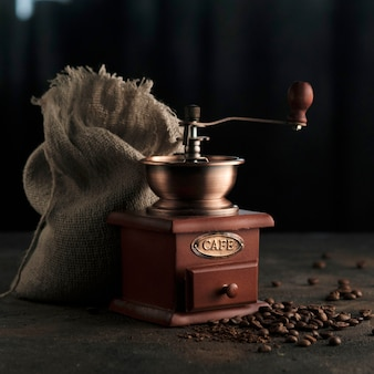 The antique vintage coffee grinder and coffee beans scattered on the table.