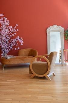 真っ赤な壁、フローリング、直射日光が当たる19世紀風のリビングルームのアンティークヴィンテージインテリア。