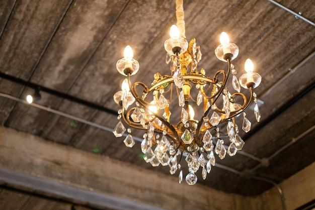 골동품 빈티지 럭셔리 클래식 스타일의 샹들리에와 반짝이는 글램 라이트가 나무 천장에 장식되어 있습니다.