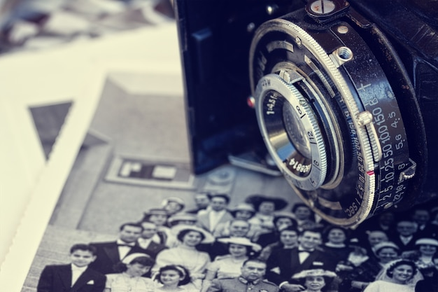 古い写真の山にアンティークのビンテージ写真カメラをクローズアップ