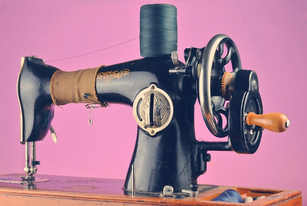 Antique, vintage sewing machine isolated on a pink pastel background