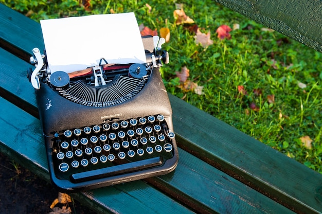 ベンチに落ち葉と秋の背景にアンティークヴィンテージタイプライター