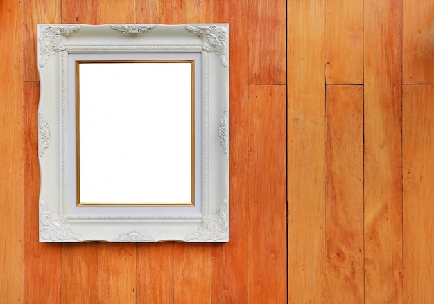 Antique white photo frame with empty space for your picture or text placed on wood plank wall background.