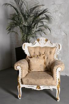 흰 벽에 식물 냄비 옆에 서있는 골동품 화이트 소파 안락의 자