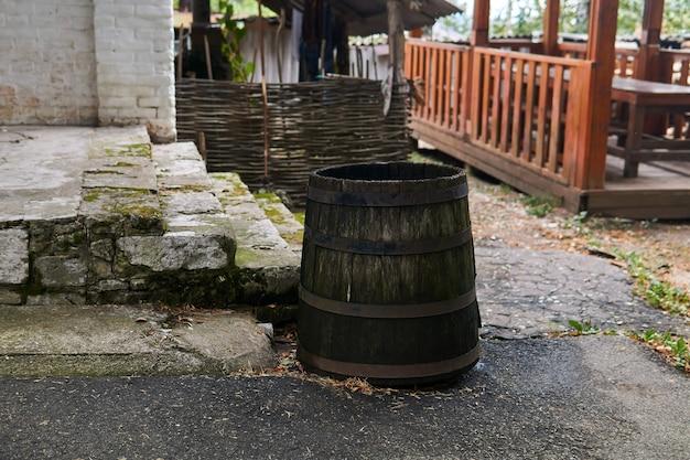 ポーチのそばに雨水を集めるためのアンティークの木製バレルが立っています