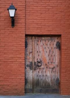 Старинная деревянная дверь с металлическими петлями на стене из красного кирпича