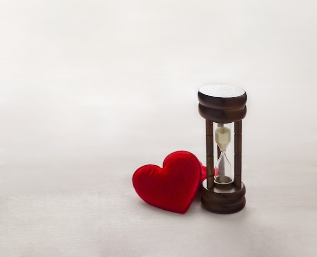 Antique wooden hourglass with red heart