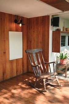 Старинное деревянное кресло-качалка с рамкой для картины и лампой на деревянной стене во внутреннем дворике с солнечным светом