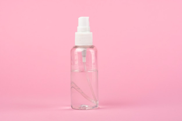 Antiseptic bottle on a pink background.