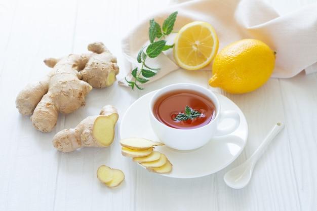 Противовирусный имбирный чай с лимоном и мятой на белом деревянном фоне. концепция здорового напитка