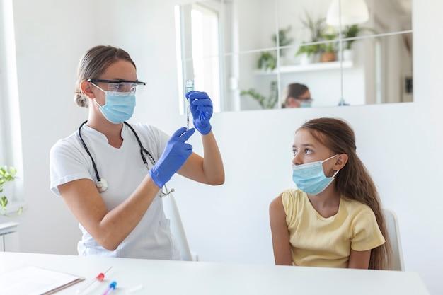 抗ウイルス免疫キャンペーンのコンセプト。医師の予防接種の女の子。 covid-19のワクチン接種を受けている医療用マスクの少女、病院でコロナウイルスワクチンの注射をしている医師。