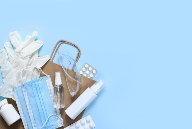 Антивирусные аксессуары: антисептик, маска, перчатки и таблетки на синем фоне. пакет из крафт-бумаги. плоский. пандемик.