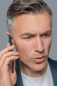 不安。灰色の背景に注意深く耳を傾ける耳の近くにスマートフォンを持つ深刻な心配の若い成人男性