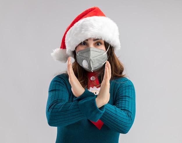サンタの帽子とサンタのネクタイが医療マスクを身に着けている気になる大人の白人女性は、コピースペースで白い壁に隔離された兆候を身振りで示す手を交差させます