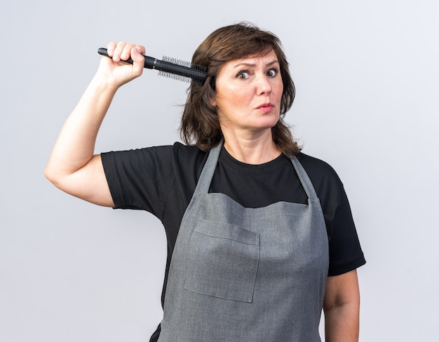 Anxious adult female barber in uniform holding comb and looking at front isolated on white wall with copy space