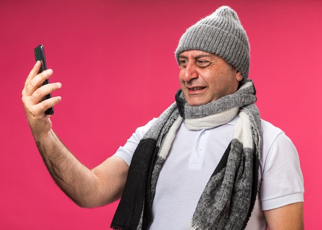 Anxious adult ill caucasian man with scarf around neck wearing winter hat holding and looking at phone isolated on pink wall with copy space