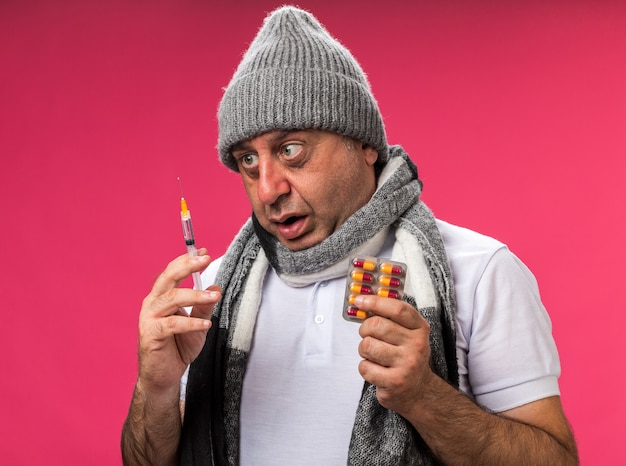 Anxious adult ill caucasian man with scarf around neck wearing winter hat holding syringe and medicine blister pack isolated on pink wall with copy space