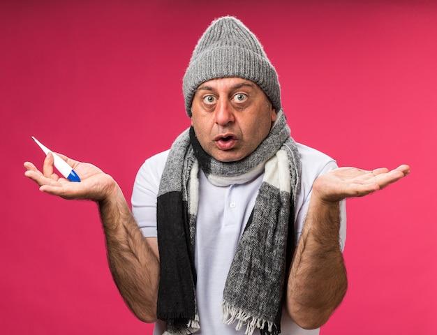 コピースペースでピンクの壁に隔離された手を開いたままにして温度計を保持している冬の帽子をかぶって首の周りにスカーフを持つ気になる大人の病気の白人男性