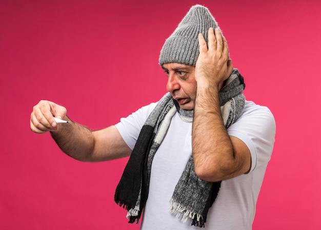 Ansioso adulto malato uomo caucasico con sciarpa intorno al collo indossando cappello invernale mette la mano sulla testa tenendo e guardando il termometro isolato sulla parete rosa con spazio di copia