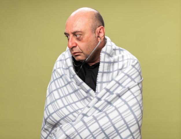 Uomo caucasico malato adulto ansioso con lo stetoscopio avvolto in un plaid guardando il lato isolato sulla parete verde oliva con lo spazio della copia