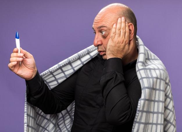 Ansioso adulto malato uomo caucasico avvolto in plaid mette la mano sul viso tenendo e guardando il termometro isolato sulla parete viola con spazio copia