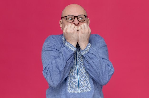 안경을 쓴 파란 셔츠를 입은 불안한 성인 남자가 옆을 바라보며 손톱을 물어뜯고 있다