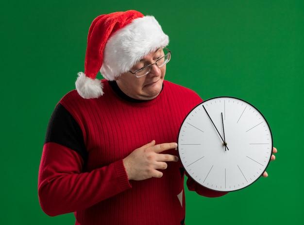 Тревожный взрослый мужчина в очках и шляпе санта-клауса держит и смотрит на часы, изолированные на зеленом фоне