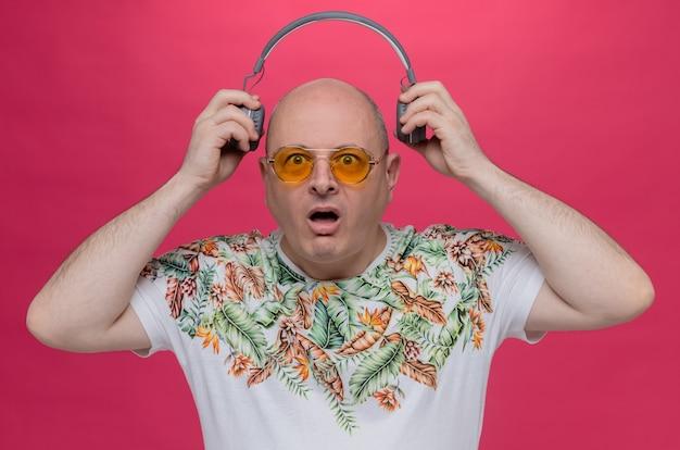 헤드폰을 들고 선글라스를 쓴 불안한 성인 남자
