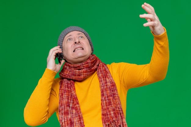 Uomo adulto ansioso con cappello invernale e sciarpa intorno al collo che parla al telefono guardando in alto