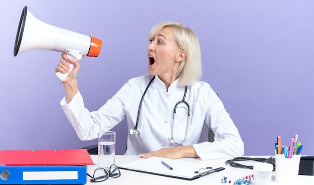 Anxious adult slavic female doctor in medical robe with stethoscope sitting at desk with office tools shouting into loud speaker looking at side isolated on purple background with copy space