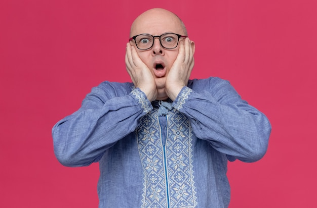 Anxious adult slavic man in blue shirt wearing glasses putting hands on his face and looking