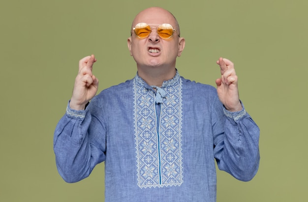 Anxious adult slavic man in blue shirt wearing sunglasses crossing fingers