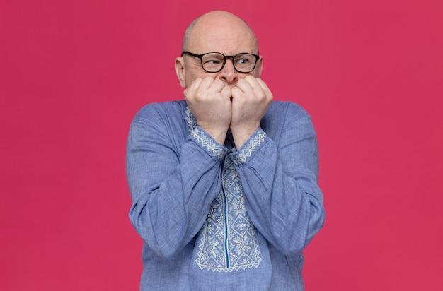 Взволнованный взрослый славянский мужчина в синей рубашке в оптических очках кусает ногти