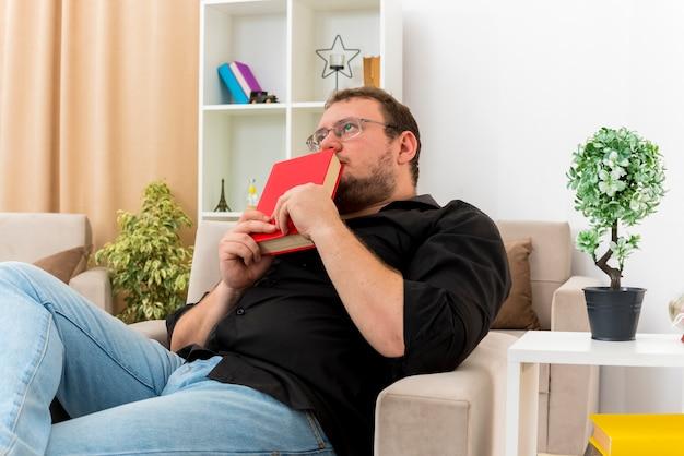 Взволнованный взрослый славянский мужчина в оптических очках сидит на кресле, держа книгу близко ко рту, глядя вверх внутри гостиной