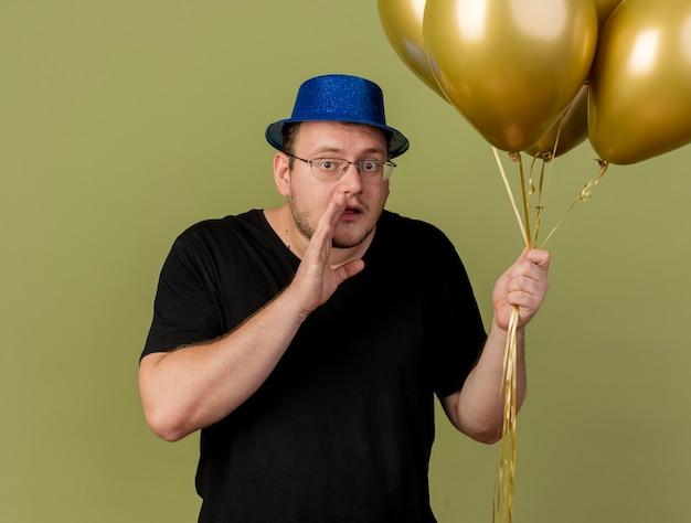 파란색 파티 모자를 쓰고 광학 안경을 쓴 불안한 성인 슬라브 남자가 손을 입 가까이에 유지하고 헬륨 풍선을 들고 있습니다.
