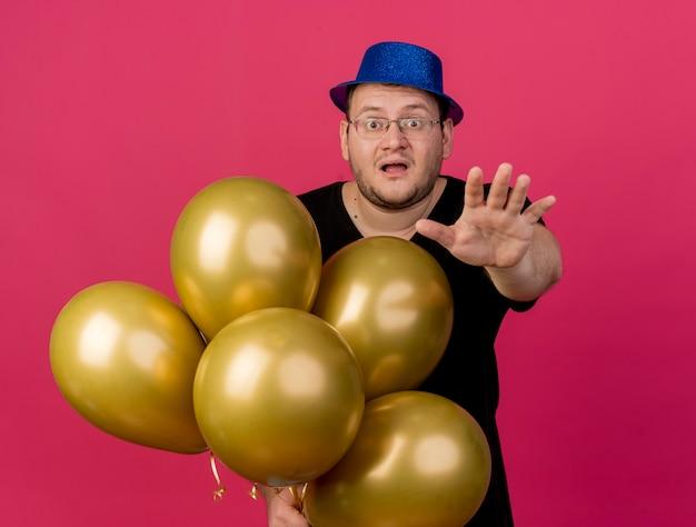 Ansioso uomo slavo adulto con occhiali ottici che indossa un cappello da festa blu tiene palloncini di elio che si allungano la mano
